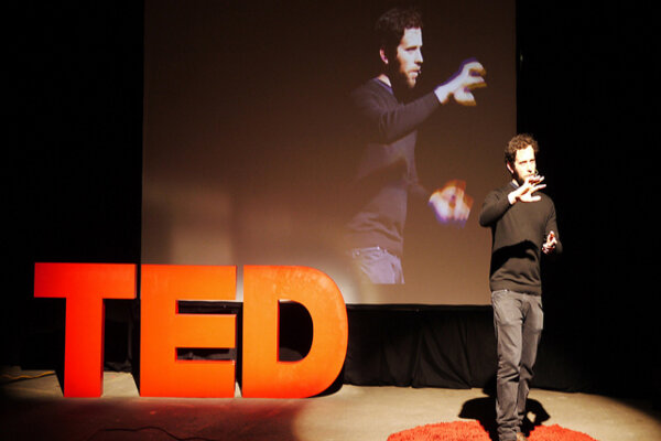Inspirational speaker in the middle of motivational TED talks for students