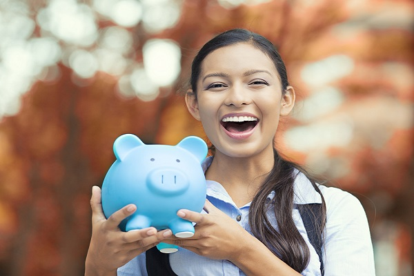 Girl student smiling and holding a piggybank. Know about the most affordable countries to study abroad.