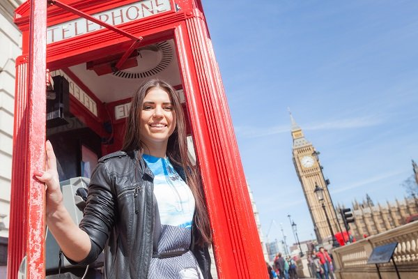 International student standing in a phonebooth in London near the big ben in the UK